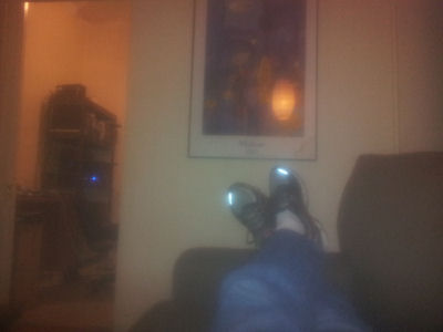 A blurry photo of my feet. I suppose red-eye reduction doesn't extend to reflective sneaker stripes.